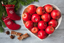 Red Apples, Basket In The Form Of Heart On A Wooden Background, Socks, Cinnamon, Anise And Branches Of A Fir