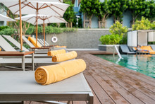 Rolled Up Orange Towel On A Sun Lounger Background Of Pool In Resort Or Hotel.