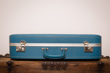 Vintage Suitcase Sitting On Old Wooden Trunk