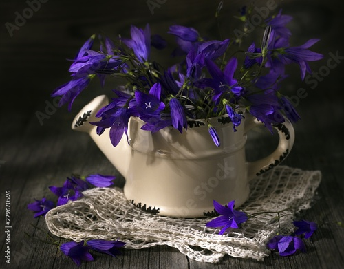 Garden Poster Pink A bouquet of blue flowers in ceramic watering on wooden table.