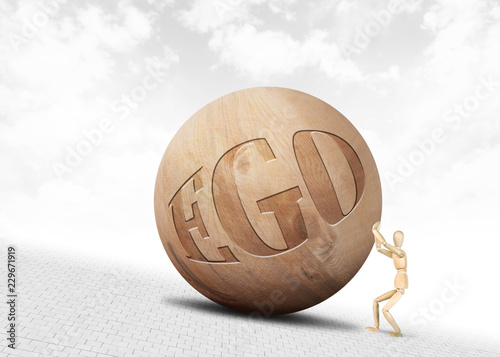 Fotografie, Obraz  Man pushes a huge wooden ball with inscription Ego upwards along the slope