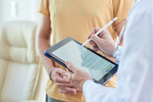 Doctor Filling Medical Card On Digital Tablet When Talking To Patient