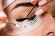 canvas print picture - Eyelash extension procedure close up. Beautiful Woman with long lashes in a beauty salon.