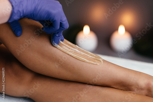Photo  Midsection of beautician waxing woman's leg at salon
