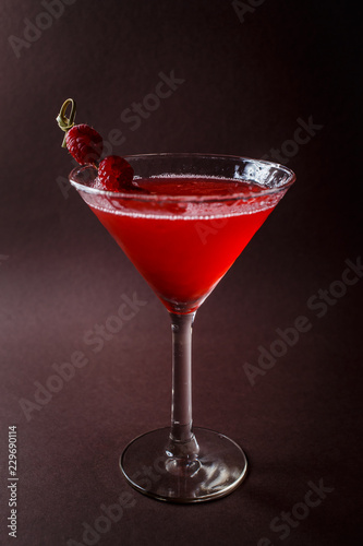 Glass of red cocktail with paspberries on elegant dark brown background