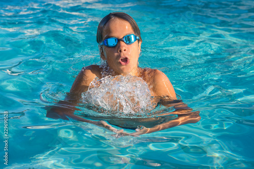 Fotografía  Close up action shot of teenage boy, young athlete swimming breaststroke