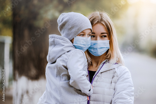 Fotografia, Obraz  a girl with a child stands on the road in a protective medical mask