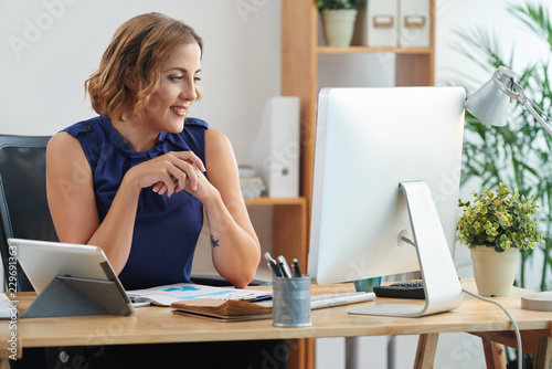 Fotografía  Smiling pretty businesswoman sitting at table in modern office and reading e-mai