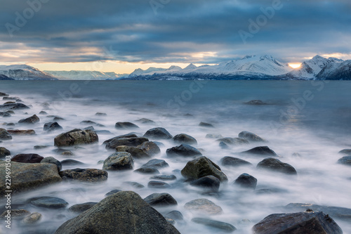 Foto op Plexiglas Noord Europa Beautiful stony seashore with blurred water and mountains on background