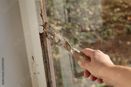 Fotomural Worker removing oil window glazing putty using putty knife tool, old window rest