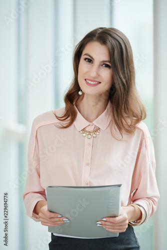 Fotografía  Smiling beautiful business woman holding folder with important documents