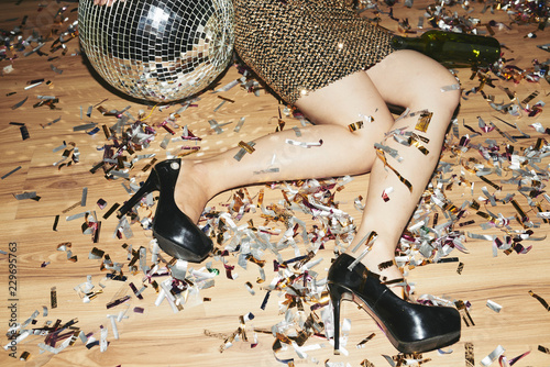 Fotografia, Obraz Cropped image of young woman in high heels and mini dress lying on the floor cov