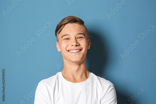 Smiling teenage boy on color background