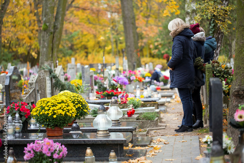 Family at the cemetery are praying at the grave Poster Mural XXL
