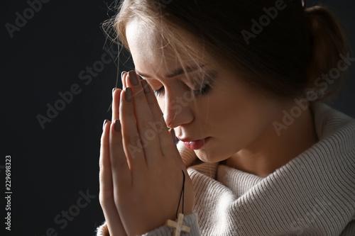 Leinwand Poster Beautiful young woman praying on dark background