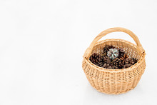 Natural Beige Color Wicker Basket With Handle, Filled With Small Colored Pine Cones, Isolated On White Snow.