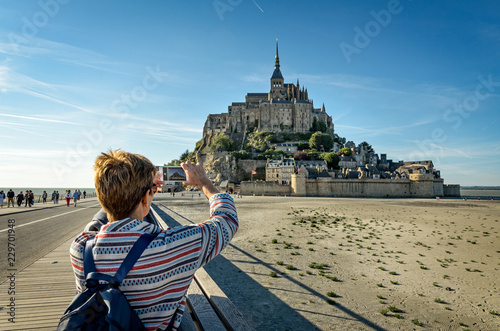 Fotografie, Obraz  A tourist takes photos of Mont Saint Michel with her smartphone