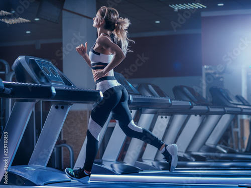 Woman trains on a treadmill in the gym Fototapeta
