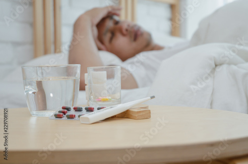 Asian men sick Lie on the white bed in the room in the morning Wallpaper Mural