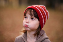 Portrait Of A Girl In A Woolly Hat Pulling Funny Faces