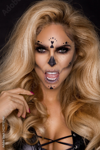 Fototapety, obrazy: Sexy blonde woman in Halloween makeup and leather outfit on a black background in the studio. Skeleton, monster
