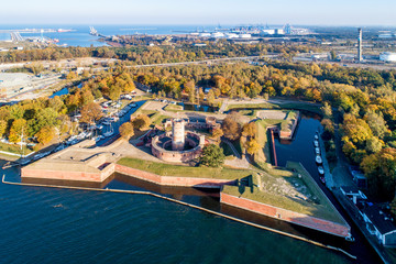 Fototapeta Medieval Wisloujscie Fortress with old lighthouse tower in port of Gdansk, Poland. A unique monument of the fortification works. Aerial view at sunset. Exterior Northern Gdansk port in the background