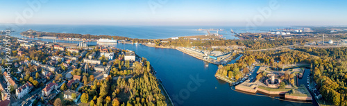 Gdansk, Poland. Wide panorama with Westerplatte peninsula, medieval Wisloujscie Fortress, Dead Vistula river mouth and Exterior Northern Port of Gdansk in the background. Aerial view in sunset light