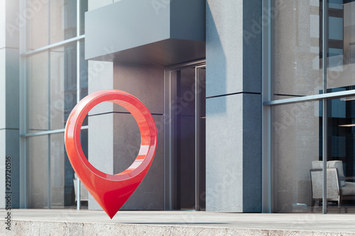 Photo Red map geotag at street next to modern glass building, 3d rendering
