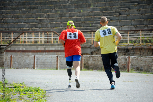 Valokuva  Disabled athlete (left) with an artificial leg running on a track