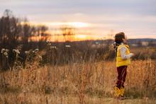Boy Standing In A Field Lookin...
