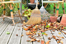 Broom And Rake In Leaves On Wo...
