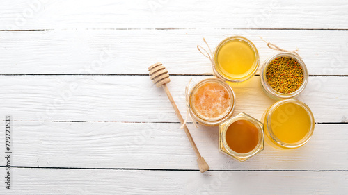 Recess Fitting Bee Set of bee products and honey on a white wooden background. Free space for text. Top view.