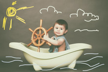 A Small Child Swims In The Imaginary Sea In Bath. Most Dream Of Becoming A Captain.