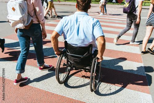 Fotografia, Obraz back view of boyfriend in wheelchair and girlfriend crossing crosswalk in city