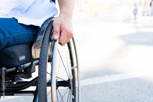cropped image of man using wheelchair on street Wallpaper Mural