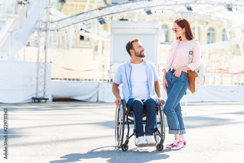 Poster Attraction parc handsome boyfriend in wheelchair and girlfriend looking at each other on street