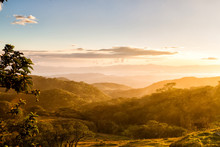 Foothills Of Monteverde, Santa Elena In Costa Rica Highlands. Panoramic View In Beautiful Orange Sunset Day Of A Vast Hills And Mountains In This Pristine Region Of Central America