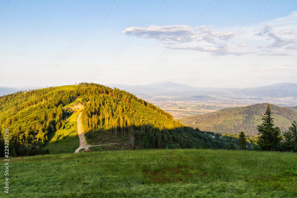 View of Klimczok peak with a mountain hostel on it. Spring panorama in Polish Beskid Slaski mountains, Europe.