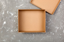 Empty Opened Brown Cardboard Box For Mock Up On Gray Cement Table With Copy Space