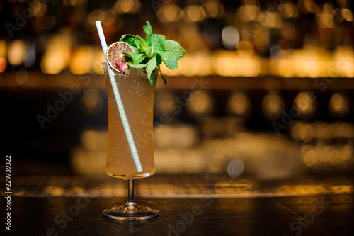 Cocktail glass filled with tasty Sherry Cobbler drink decorated with mint, straw and orange slice