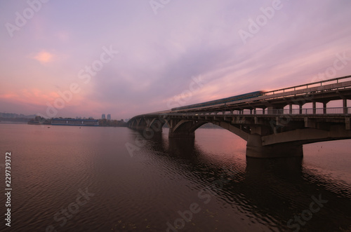 Keuken foto achterwand Kiev Merto Bridge with old underground train over Dnipro River. Scenic autumn landscape during sunrise. Colorful vibrant sky reflected in the water. Selective focus with wide angle lens. Kyiv, Ukraine