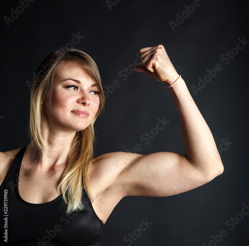Attractive fitness woman is showing her biceps on black background Canvas Print
