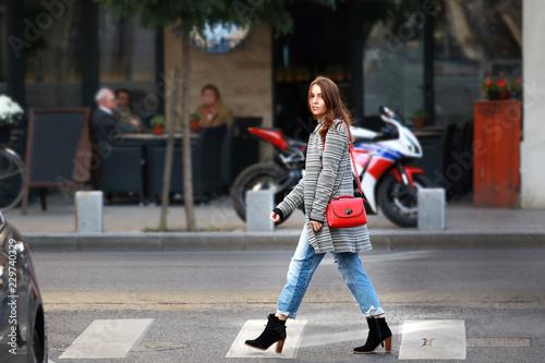 Urban style: Stylish beautiful eastern European young woman crossing street Poster Mural XXL
