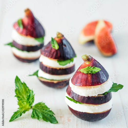 Ready-to-eat fun appetiezer with figs, cheese, purple basil, mint leaves. Ideas and recipes for healthy breakfast, dinner, appetiezer, salad. Can use for design cheese dairy.Copy space for text.Square