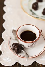 Coffee And Heart Shaped Chocolate Pralines On Table