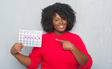 Young African American Woman Over Grey Grunge Wall Holding Menstruation Calendar Very Happy Pointing With Hand And Finger