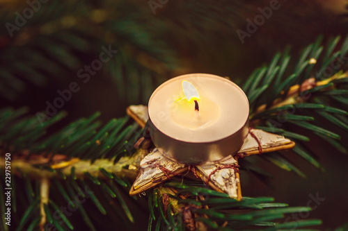 Fotografía  Old fashioned picture of tea candle glowing on star shaped ornamental holder pla