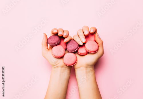 Foto auf AluDibond Macarons Beautiful female hands with trendy manicure holding pink macaroon cake.