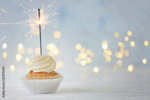 Fotografia  Delicious cupcake with sparkler on white table against blurred lights
