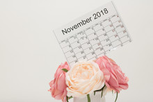 Calendar Of November 2018 With Holiday Date Of Thanksgiving Day And Lunar Days Is On Above Bouquet Of Pastel-colored Flowers On White Background.